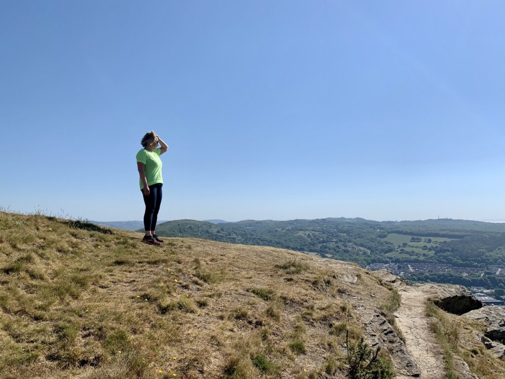 Maren standing on top of the Garth Hill in South Wales near Cardiff, looking out over  summer landscape.
