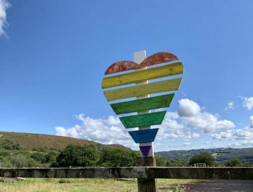 The image shows a landscape with blue sky and a heart-shaped wooden sign in rainbow colours.